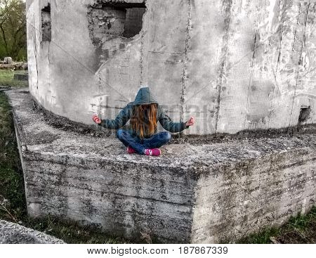 A girl with long blond hair in a hood sits in a lotus pose. She sits outdoors on a concrete wall and tilted her head down