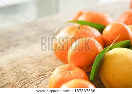 Appetizing fresh citrus fruits with green leaves on wooden table
