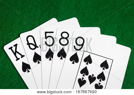 casino, gambling, games of chance, hazard and entertainment concept - poker hand of playing cards on green cloth