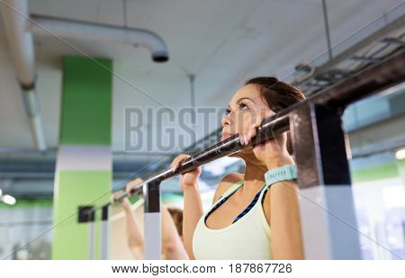 sport, fitness and people concept - woman exercising and doing pull-ups at horizontal bar in gym