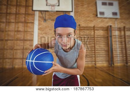 Determined high school boy playing basketball in the court