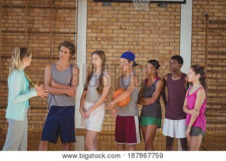 Portrait of female coach mentoring high school kids in basketball court