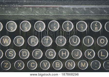 Close-up horizontal shot of a dusty obsolete typewriter keyboard.