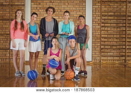Portrait of high school kids with basketball standing together in basketball court