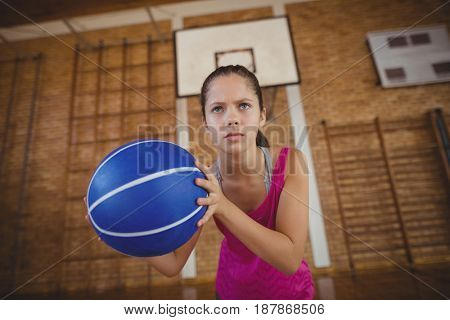 Determined high school girl playing basketball in the court