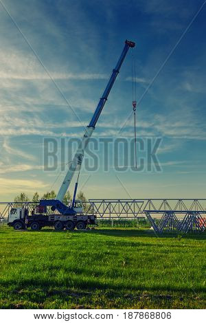 Car crane with risen telescopic boom outdoors on the construction site.