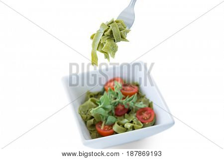 Close-up of pasta salad in bowl with fork on white background