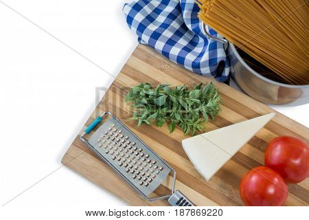 Food and grater on cutting board against white background
