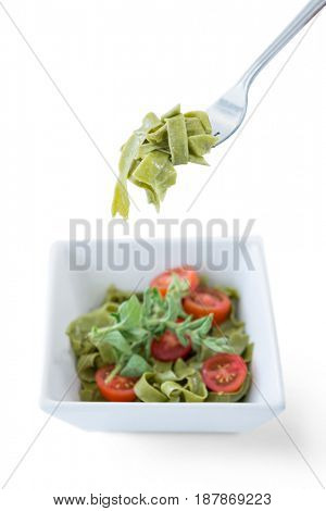 Close-up of pasta salad in bowl with fork against white background