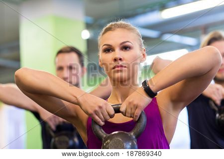 sport, fitness, weightlifting and people concept - woman with kettlebell and heart-rate tracker at group training exercising in gym