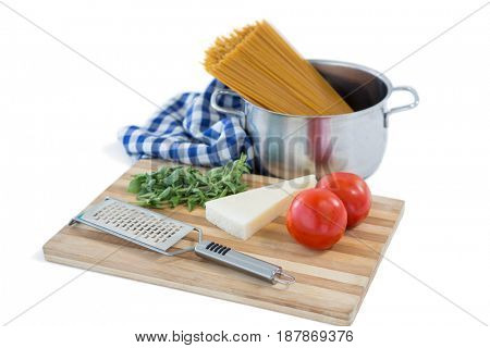 Food with cutting board and grater against white background
