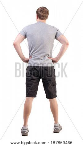 Back view of handsome man in t-shirt and  shorts  looking up.   Standing young tourist. Rear view people collection.   Isolated over white background. athlete demonstrates his broad back
