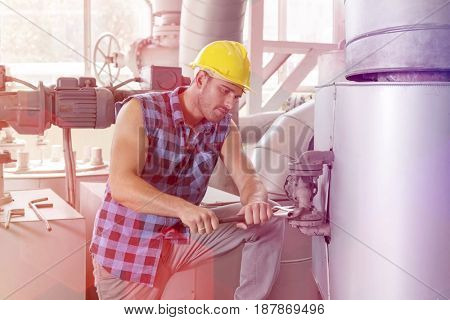 Young manual worker using wrench on industrial machine
