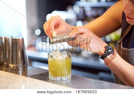 alcohol drinks, people and luxury concept - close up of woman bartender with glass and grater grates white chocolate preparing cocktail at bar