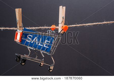 Close-up View Of Small Shopping Cart With Sale Sign Hanging On Rope Isolated On Grey, Big Sale Conce