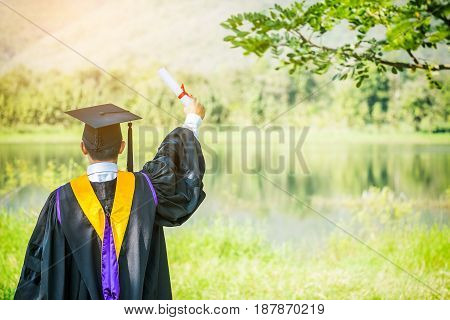 Graduate put he hands up and celebrating with certificate in he hand and feeling so happiness in Commencement day.
