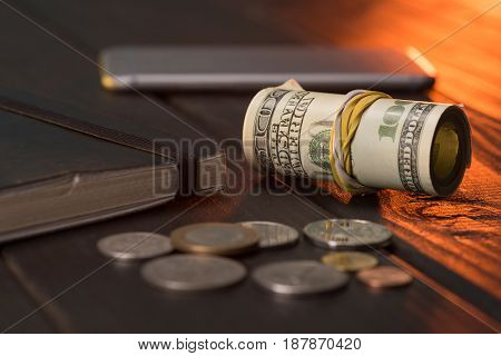 us dollars and coins with notebook and smartphone on wooden table pile of coins