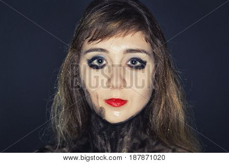 Young girl's face with bright makeup on dark background