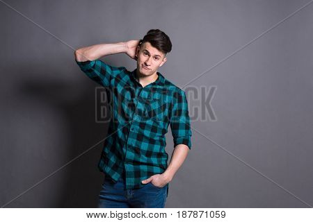 Young man model studio portrait. Boy casual style, trendy hipster in checkered shirt look with cool hairstyle