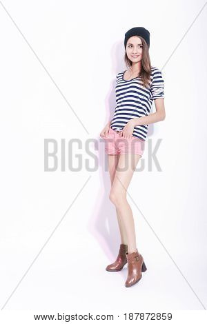 Fashion and Lifestyle Concepts. Full Length Portrait of Smiling Brunette Girl in Hat and Striped Shirt. Posing on High Heels Against White. Vertical Composition