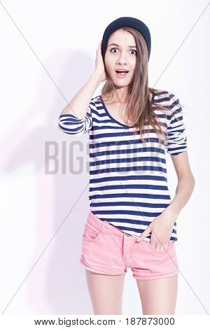 Youth LIfesttyle Ideas. Portrait of Surprised Slim Caucasian Brunette Girl With LIfted Hand. Touching Hat. Posing in Striped Shirt Against White.Vertical Image Orientation