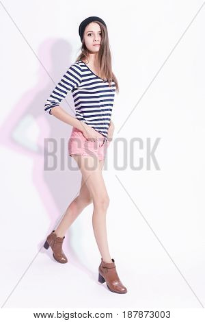 Full Length Portrait of Walking Caucasian Brunette in Warm Hat and Striped Shirt. Posing in High Heels Against White.Vertical Image Orientation