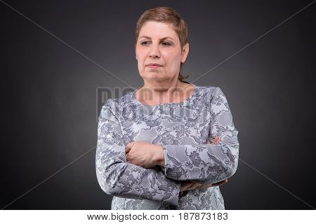 Portrait of puzzled senior woman on dark background