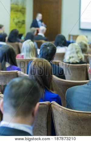 Group of Professionals Attending Business Conference. Sitting in Front of The Speaking Male Host in Front.Vertical Image