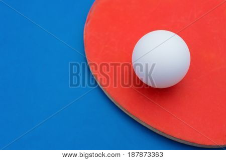 pingpong rackets and ball on a blue table cloes up
