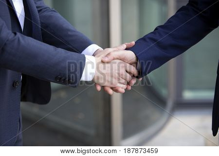 two businesssmen standing outside and shaking hands