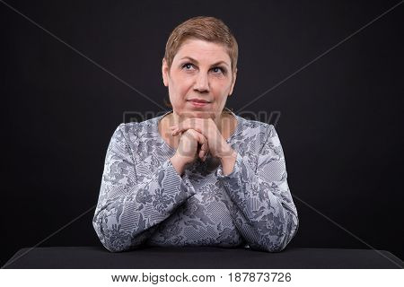 Portrait of sitting thinking senior woman on black background