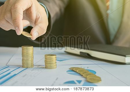 Money Financial Business Growth concept Business man's hand put money coins to stack of coins.