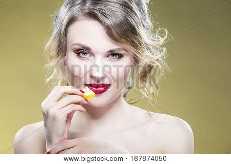 Portrait of Sexy Caucasian Blond Girl Eating With Tiny Lemon Piece. Showing Satisfied and Alluring Facial Expression. Against Yellow Background.Horizontal Image Orientation