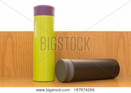 green and black vacuum tumblers on a wood table