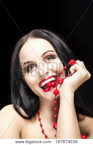 Portrait of Funny Caucasian Brunette Woman Biting Her Long Red Beads and Smiling Against Black Background. Vertical Image