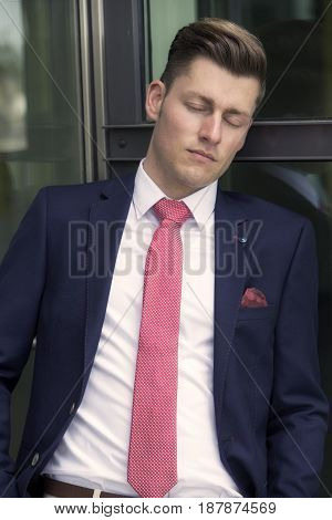 handsome man in suit leaning against window with his eyes closed