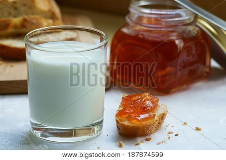 A glass of milk with a piece of bread and apple jam.