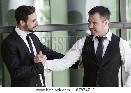 two businessmen standing outside and shaking hands