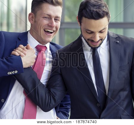 two businessmen outside smiling and shaking hands