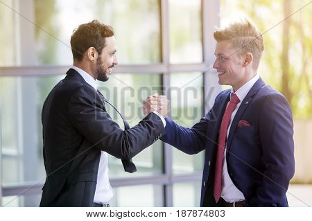 two businessmen standing outside smiling and shaking hands