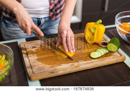 Woman preparing vegetable salad in the kitchen at the table with knife