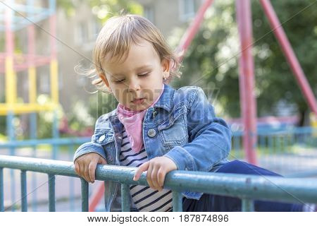 Little beautiful girl on the playground passes the over railing
