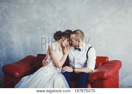 Bride and groom hugging on a sofa in loft