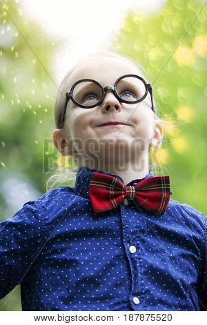 portrait of young boy with bow tie and big black glasses