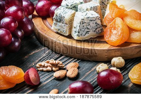 Cheese plate with fruits and nuts on a wooden table