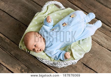Basket with baby, wooden background. Small surprised child. This new world around me.