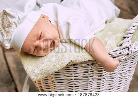 Crying baby close up. Upset child lying on basket. Reasons why babies cry.