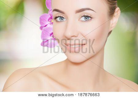 portrait of young caucasian woman with purple otchids spa concept
