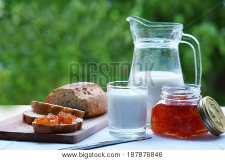 A decanter with milk and a glass of milk. Bread is smeared with jam. Jar of apple jam. Green background