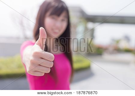 woman thumb up and smile happily in the park